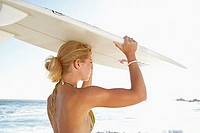 Young woman standing on beach in bright sunlight, carrying surfboard on head, side view