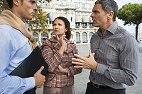 Spain, Barcelona, two men and woman talking in city plaza, side view
