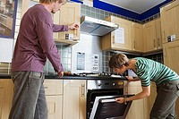 Couple looking at new kitchen in home furnishings store, man opening cupboard, woman checking oven (thumbnail)