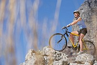 Female mountain biker standing at edge of rock, side view, low angle view