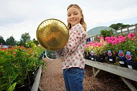 Blonde girl 7-9 holding watering can in garden centre, smiling, portrait (thumbnail)