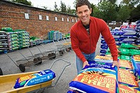 Man loading compost into trolley in garden centre, smiling, portrait