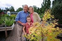 Girl 7-9 standing with grandparents behind plant on trolley in garden centre, smiling, portrait