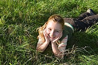 Girl 7-9 lying on grass, resting hands on chin, smiling, close-up, portrait