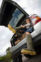 Boy 8-10 putting on wellington boots, sitting in boot of stationary car, smiling, portrait, low angle view tilt