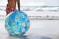 Teenage boy 13-15 standing on sandy beach behind large blue beach ball, low section