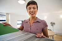 Female office worker standing beside filing cabinet, smiling, portrait