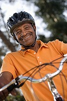 Active senior man wearing orange polo shirt and cycling helmet, sitting on bicycle in park, smiling, portrait, close-up, low angle view tilt