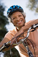 Active senior woman wearing polo shirt and cycling helmet, sitting on bicycle in park, smiling, portrait, close-up, low angle view tilt