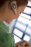 Woman wearing mobile phone hands-free device on ear, side view, close-up tilt, differential focus