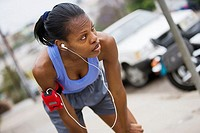 Exhausted female jogger stopping for breath on pavement, leaning on knees, listening to MP3 player strapped to arm, focus on foreground tilt