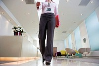 Businesswoman walking through lobby, carrying pink folder, low section, front view, surface level