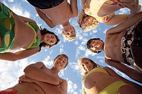 Group of teenagers 13-15 standing in circle, smiling, portrait, upward view