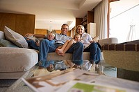Two generation family relaxing on sofa at home, smiling, front view, portrait (thumbnail)