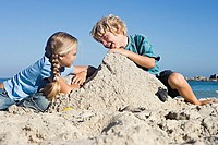 Boy 4-6 and girl 6-8 building sandcastles on sandy beach, smiling, side view