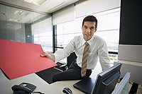 Businessman leaning on desk in office, passing red file, smiling, portrait