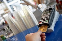 Customer placing bank card in credit card reader, close-up, rear view, personal perspective tilt