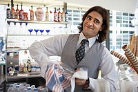 Waiter wiping glass with dishtowel behind bar, smiling, portrait blurred motion