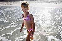 Girl 6-8 wearing bikini, standing in sea at beach, smiling