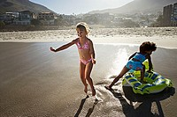 South Africa, Cape Town, two girls 6-10 playing with inflatable toy on sandy beach, smiling
