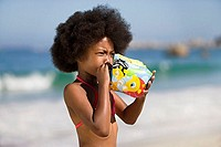 Girl 8-10 blowing air into inflatable armband, standing on sandy beach, side view