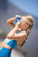 Blonde girl 6-8 taking photograph with blue camera on beach, side view tilt