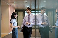 Businessman and businesswoman talking in office corridor, smiling, side view, reflection in glass