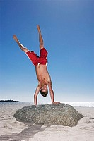Teenage boy 17-19 in red swimming shorts doing handstand on top of beach rock, smiling, portrait