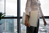 Businesswoman standing beside window, carrying laptop underarm, side view, mid-section