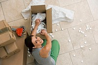 Woman sitting on floor, packing box with paper and foam, smiling, portrait, overhead view