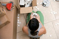 Woman sitting on floor, packing box, wrapping bowl in paper, overhead view