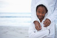 Mother and daughter 8-10 in white clothing standing on beach, smiling, front view, portrait