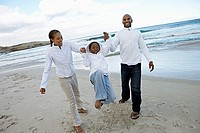 Parents swinging daughter 8-10 on beach, smiling, family wearing white clothing tilt