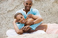 Couple relaxing on rocky beach, woman lying in man´s lap, smiling, portrait