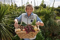 Senior woman standing in garden holding fresh basket of vegetables, smiling, front view, portrait