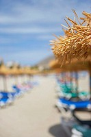 Palapa sunshades and sunloungers on sandy beach, focus on foreground