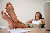 Businesswoman relaxing in office, sitting with bare feet up on desk, focus on foreground