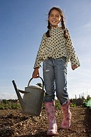Girl 9-11 in pink boots carrying watering can in garden, smiling, portrait, low angle view