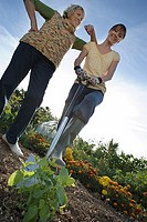 Two women standing with spade in garden, smiling, portrait, low angle view tilt