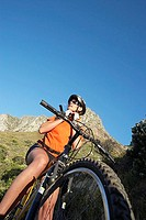 South Africa, female mountain biker adjusting cycling helmet strap, low angle view tilt