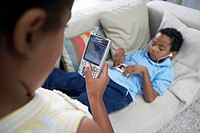 Two children 7-10 relaxing at home, boy on sofa listening to MP3 player, girl holding mobile phone