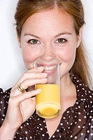 Young woman drinking glass of orange juice, smiling, close-up, front view, portrait