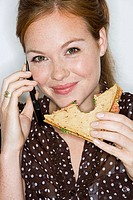 Young businesswoman eating sandwich, wearing telephone headset, smiling, close-up