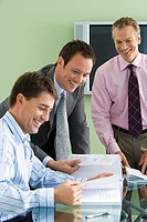 Three businessmen sitting and standing at desk in office, looking at documents, laughing