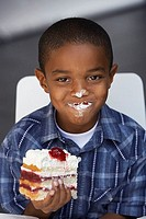 Boy 7-9 eating slice of cream cake, whipped cream on lips and nose, smiling, close-up, portrait