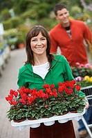 Couple shopping in garden centre, focus on woman carrying tray of red flowers in foreground, smiling