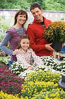 Family shopping for flowers in garden centre, man holding pot plant, smiling, portrait