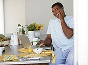 Man sitting at breakfast table in kitchen, using laptop and mobile phone, smiling, side view