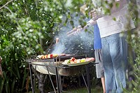Man cooking sausages and kebab on barbeque grill in garden, holding tongs, side view