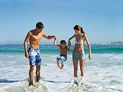 Parents swinging son 5-7 in surf on beach, in smiling, front view